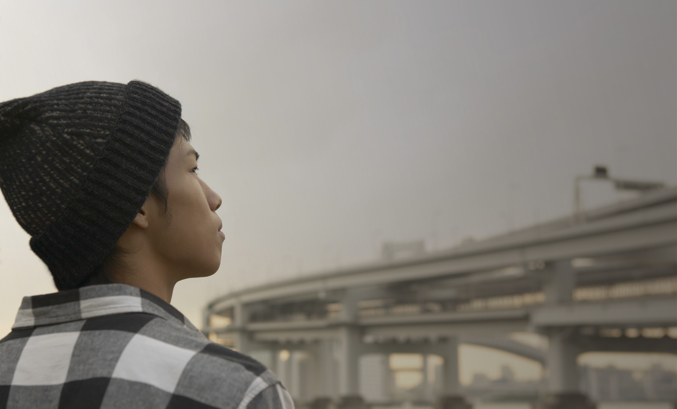 Young man in an urban setting looks toward the horizon   Jeune homme en milieu urbain regarde vers l'horizon